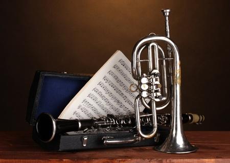 instrumentos musicales: trompeta y clarinete antiguo en caso de sobre la mesa de madera sobre fondo marr�n Foto de archivo