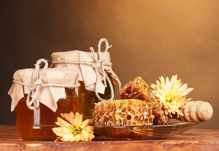 two jars of honey,honeycombs and wooden drizzler on table on yellow background Stock Photo - 12848226
