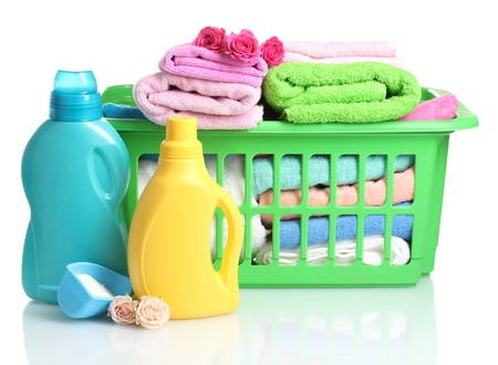 Detergents and towels in green plastic basket isolated on white photo