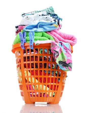 Clothes in orange plastic basket isolated on white photo