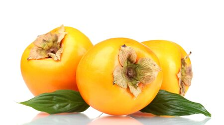Three appetizing persimmons with green leaves isolated on white photo