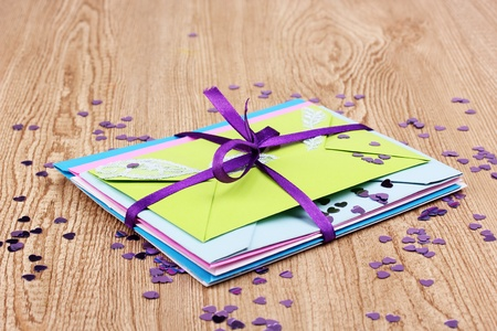 Bunch of color envelopes with ribbon and confetti on wooden background Stock Photo - 12848239