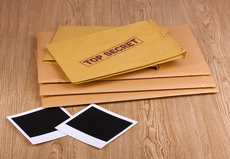 Envelopes with top secret stamp with photo papers on wooden background Stock Photo - 12848127