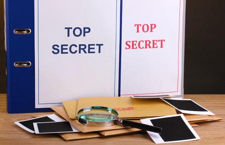 Envelopes and folders with top secret stamp and magnifying glass with photo papers on wooden table on brown background photo