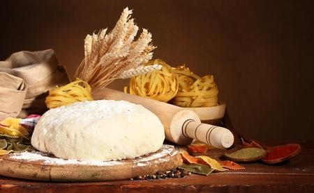 amasando: ingredientes para la pasta hecha en casa en la mesa de madera sobre fondo marr�n
