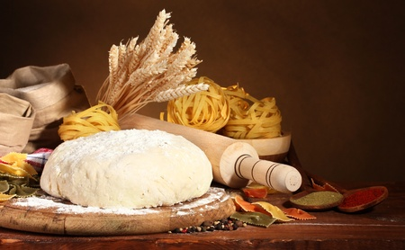 knead: ingredients for homemade pasta on wooden table on brown background Stock Photo