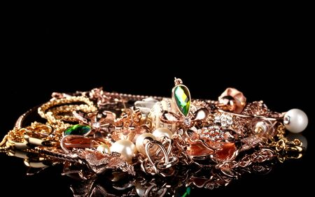 Various gold jewellery on black photo