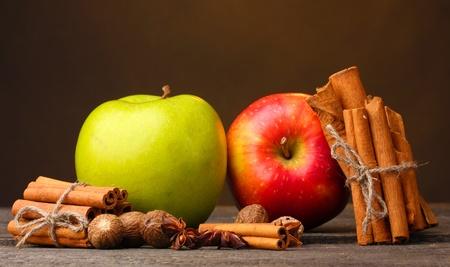 Ramas de canela, manzanas nuez moscada y anís en la mesa de madera sobre fondo marrón