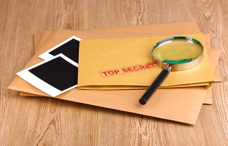 Envelopes with top secret stamp with photo papers and magnifying glass on wooden background Stock Photo - 12915070