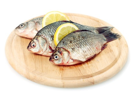Fresh fishes with lemon on wooden cutting board isolated on white photo