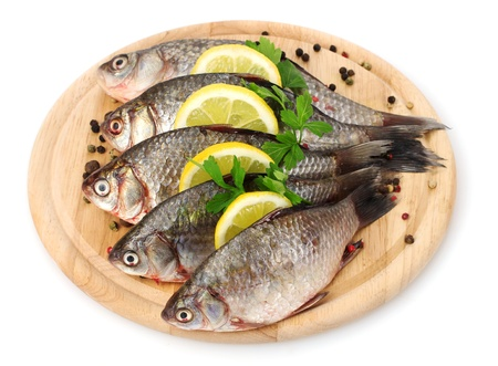 Fresh fishes with lemon, parsley and spice on wooden cutting board isolated on white Stock Photo - 12914779
