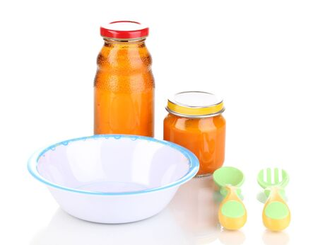 Jar of baby puree and juice with plate, spoon and fork isolated on white photo