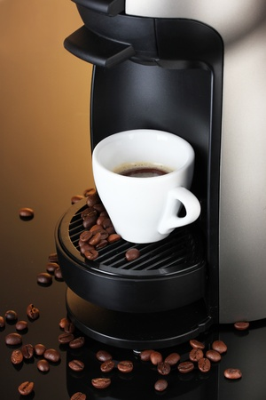 Espresso machine and cup of coffee on brown background photo