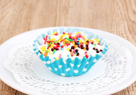 Creamy cupcake on saucer on wooden background photo