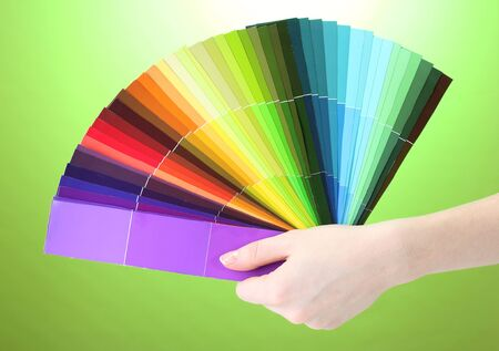 hand holding bright palette of colors on green background Stock Photo - 12914245