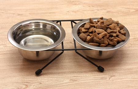 dry dog food and water in metal bowls on wooden background photo