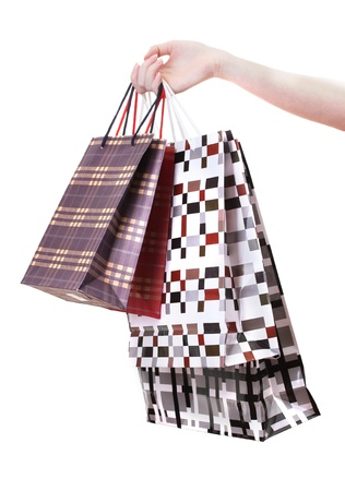 Female hand holding bright shopping bags isolated on white photo