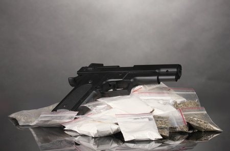 Cocaine and marihuana in packages and handgun on grey background photo