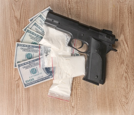 illicit: Cocaine in packages, dollars and handgun on wooden background