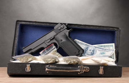 Cocaine, marijuana dollars and handgun in case on wooden table on grey background Stock Photo - 13085235
