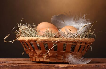 chicken eggs in a nest on wooden table on brown background photo