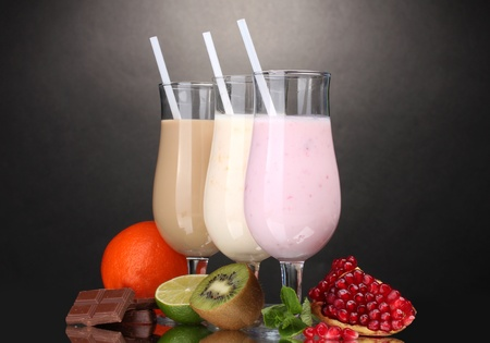 Milk shakes with fruits and chocolate on grey background photo
