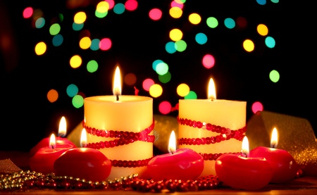 luz de velas: Hermosas velas y la decoraci�n en la mesa de madera sobre fondo brillante