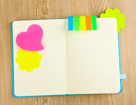 stickies: Open note book with stickies on wooden background Stock Photo