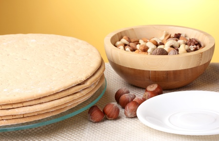 cakes for cake on glass stand and nuts on table on yellow background photo