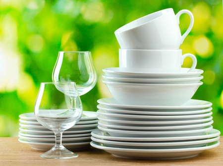 tableware: Clean dishes on wooden table on green background
