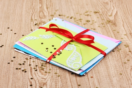 Bunch of color envelopes with ribbon and confetti on wooden background Stock Photo - 13084784