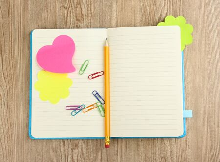 Open note book with stickies and pencil on wooden background photo