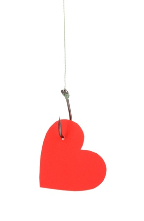 Heart on fish hook isolated on white photo
