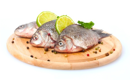 Fresh fishes with lime, parsley and spice on wooden cutting board isolated on white photo