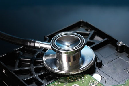 Stethoscope on hard disk drive on dark blue background photo