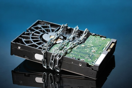 corrupt practice: Hard disk drive on chain on dark blue background