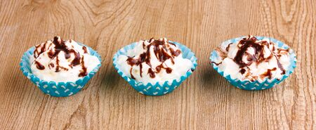 Creamy cupcakes on wooden background photo