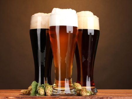 schwarzbier: drei Gl�ser mit verschiedenen Biersorten und Hopfen auf Holztisch auf braunem Hintergrund Lizenzfreie Bilder