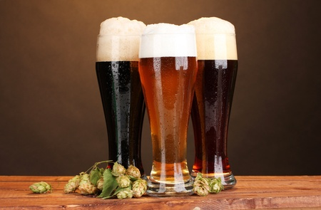three glasses with different beers and hop on wooden table on brown background photo