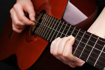 fretboard: Guitar in hands isolated on black Stock Photo