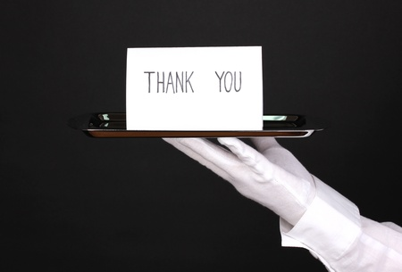 Hand in glove holding silver tray with card saying thank you isolated on black Stock Photo - 13083591