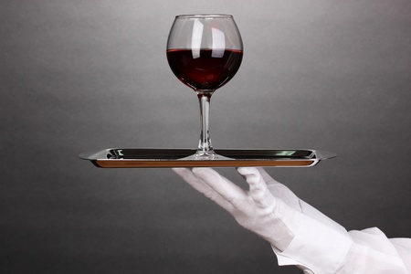Hand in glove holding silver tray with wineglass on grey background photo