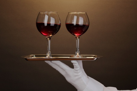 Hand in glove holding silver tray with wineglasses on brown background Stock Photo - 13084259