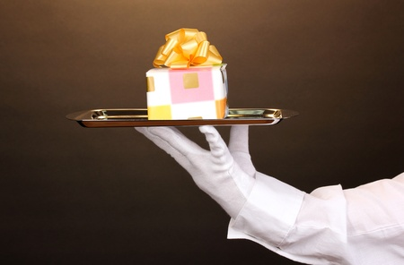 Hand in glove holding silver tray with giftbox on brown background Stock Photo - 13084569