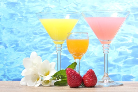 exotic cocktails, strawberry and flowers on table on blue sea background photo