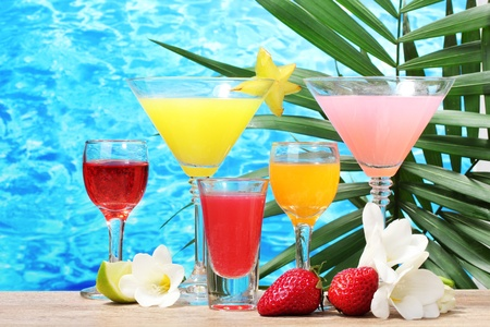exotic cocktails and flowers on table on blue sea background Stock Photo - 13084877