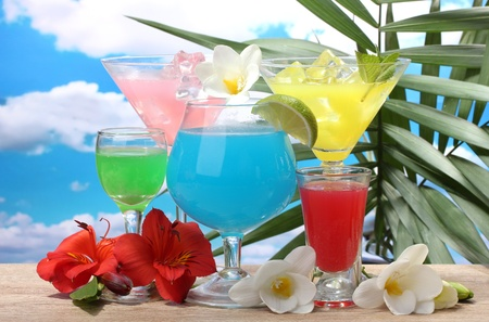 blue hawaiian drink: exotic cocktails and flowers on table on blue sky background