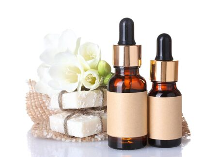 aromatherapy oils: bottles with essence oil, soap and flower isolated on white