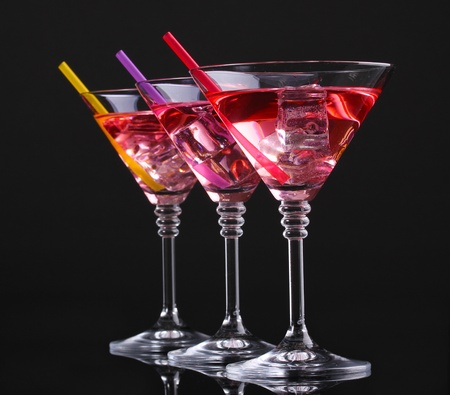 Red cocktail in martini glasses isolated on black photo