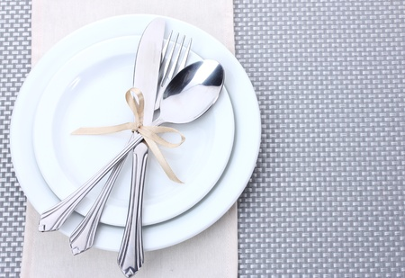 fork knife spoon: White empty plates with fork, spoon and knife tied with a ribbon on a grey tablecloth